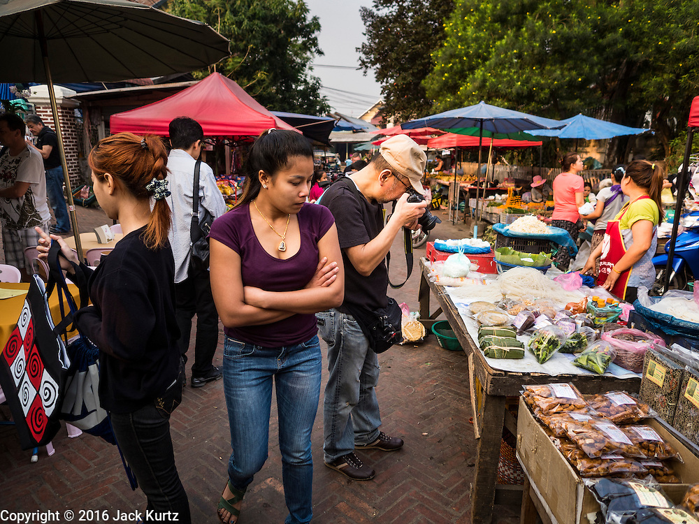 "13 MARCH 2016 - LUANG PRABANG, LAOS: A tourist photographs a noodle stand in the market in Luang Prabang while shoppers walk around him. Luang Prabang was named a UNESCO World Heritage Site in 1995. The move saved the city's colonial architecture but the explosion of mass tourism has taken a toll on the city's soul. According to one recent study, a small plot of land that sold for $8,000 three years ago now goes for $120,000. Many longtime residents are selling their homes and moving to small developments around the city. The old homes are then converted to guesthouses, restaurants and spas. The city is famous for the morning ""tak bat,"" or monks' morning alms rounds. Every morning hundreds of Buddhist monks come out before dawn and walk in a silent procession through the city accepting alms from residents. Now, most of the people presenting alms to the monks are tourists, since so many Lao people have moved outside of the city center. About 50,000 people are thought to live in the Luang Prabang area, the city received more than 530,000 tourists in 2014.    PHOTO BY JACK KURTZ"