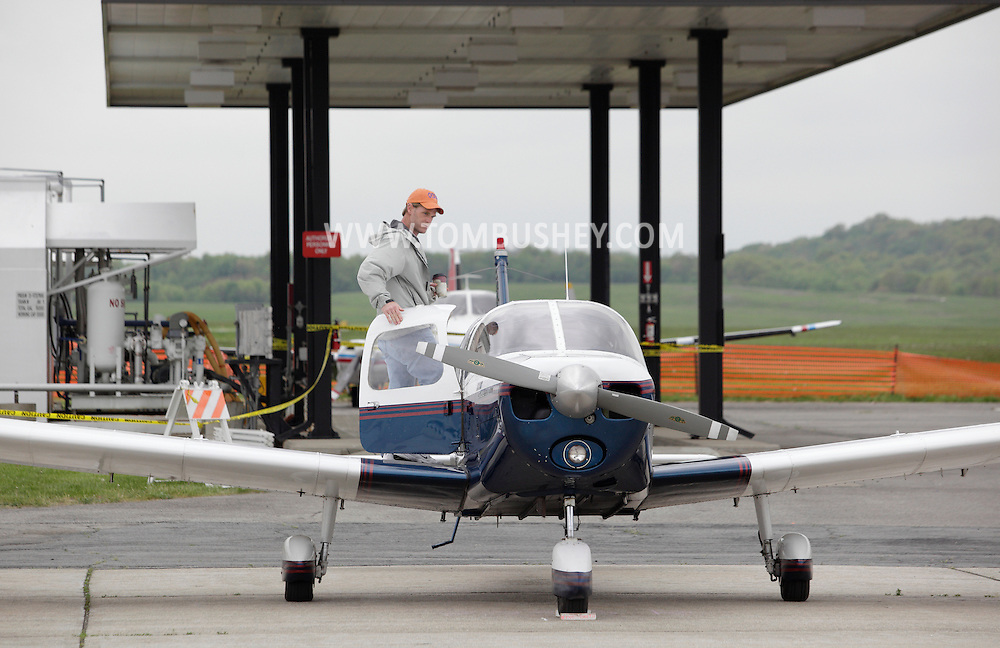 Montgomery, New York - A pilot stands on the wing of an airplane at Orange County Airport on May 14, 2011.