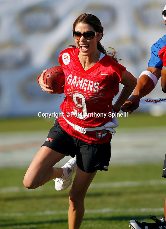 Actress Shannon Elizabeth (09) of the Gamers team runs the ball as she plays flag football in the EA Sports Madden NFL 11 Launch celebrity and NFL player flag football game held at Malibu Bluffs State Park on July 22, 2010 in Malibu, California. (©Paul Anthony Spinelli)