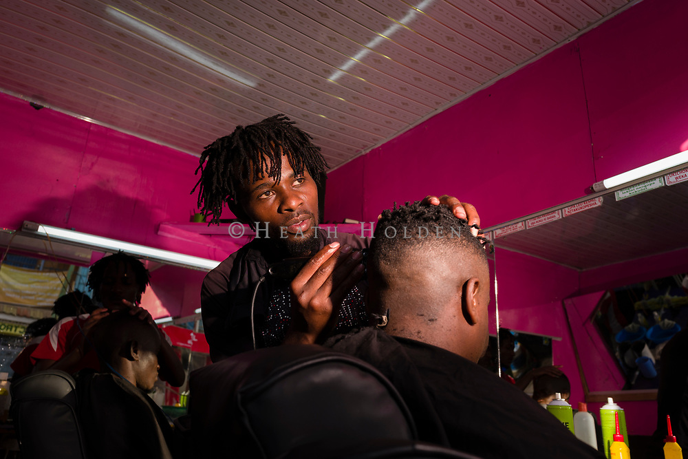 A male barber trims a cuistomers hair in the vibrant town of Kibera in Nairobi Kenya on Wednesday 18th of September.