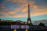 The Bateaux-Mouches sign is illuminated at dusk in front of the Eiffel Tower. The Bateaux-Mouches, the iconic excursion boats on the river Seine, and the Eiffel Tower are two of the most popular attractions for visitors to Paris. http://www.gettyimages.com/detail/photo/bateaux-mouches-sign-and-eiffel-tower-at-high-res-stock-photography/516032919