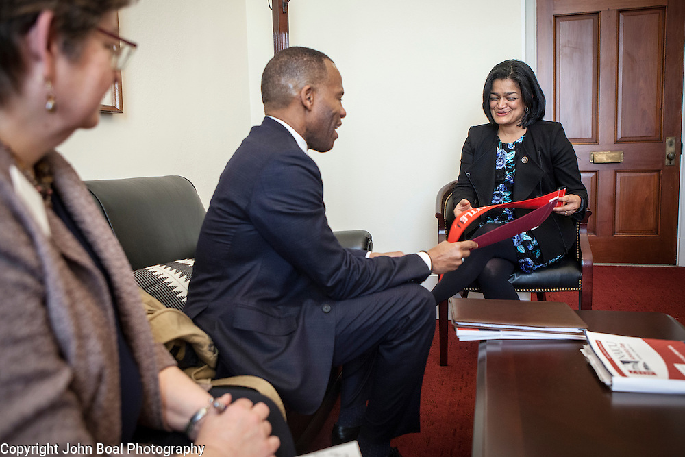 Representative Pramila Jayapal (D-WA, 7) receives a pennant of Seattle University from Isiaah Crawford, and Violet Boyer, left, of the National Association of Independent Colleges and Universities, on Tuesday, January 31, 2017.  This was the last of 4 30-minute meetings with constituent advocacy groups during the day.  John Boal photo/for The Stranger