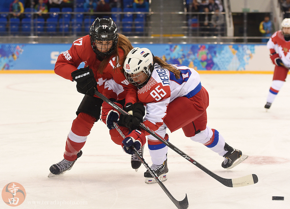 Feb 15, 2014; Sochi, RUSSIA; Switzerland forward Jessica Lutz (17) and Russia forward Yelena Dergachyova (95) battle for the puck in a women's quarterfinals ice hockey game during the Sochi 2014 Olympic Winter Games at Shayba Arena.