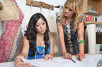 Female fashion designers working at desk
