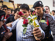 "14 FEBRUARY 2015 - BANGKOK, THAILAND: Student activist Siriwit Serithiwat holds up a rose while he is led away by police after he was arrested during a protest the military coup. Martial law is still in effect in Thailand and protests against the coup are illegal. Dozens of people gathered in front of the Bangkok Art and Culture Centre in Bangkok Saturday to hand out red roses and copies of George Orwell's ""1984."" Protestors said they didn't support either Red Shirts or Yellow Shirts but wanted a return of democracy in Thailand. The protest was the largest protest since June 2014, against the military government of General Prayuth Chan-Ocha, who staged the coup against the elected government. Police made several arrests Saturday afternoon but the protest was not violent.      PHOTO BY JACK KURTZ"