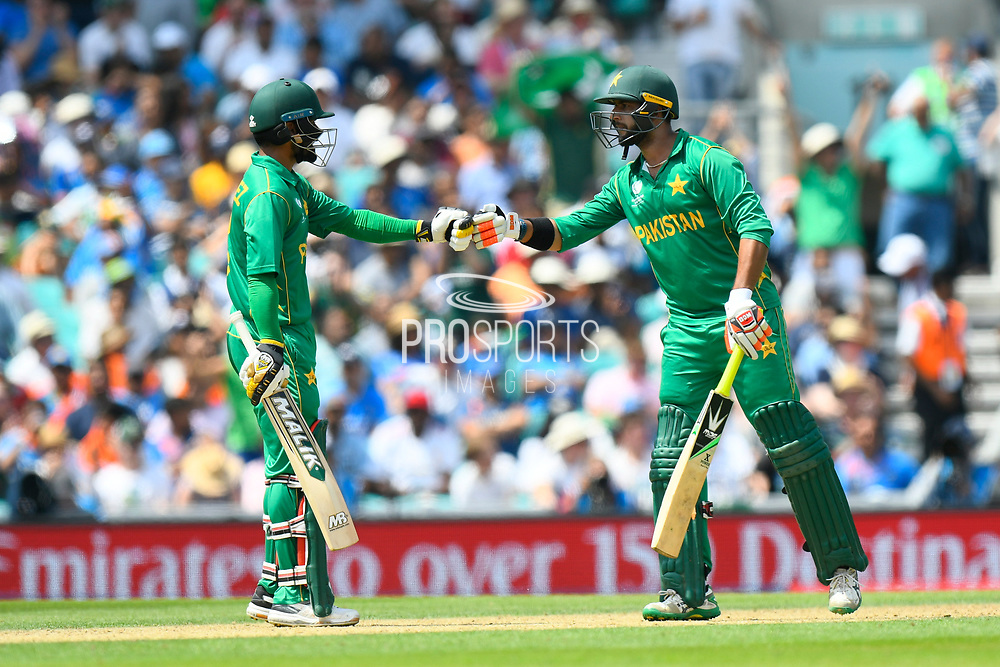 Mohammad Hafeez of Pakistan and Imad Wasim of Pakistan touch gloves after Wasim hit a six during the ICC Champions Trophy final match between Pakistan and India at the Oval, London, United Kingdom on 18 June 2017. Photo by Graham Hunt.