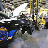 Thomas Wells | BUY at PHOTOS.DJOURNAL.COM<br /> Carl Roebuck uses a forlift to lift the front end of a Tupelo Police Car and guide it into the bay so he can replace the moto and get it back on the streets.