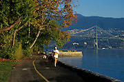 Woman jogging on Seawall Promenade in Stanley Park, Vancouver, British Columbia, Canada. Lions Gate Bridge and North Vancouver in background.