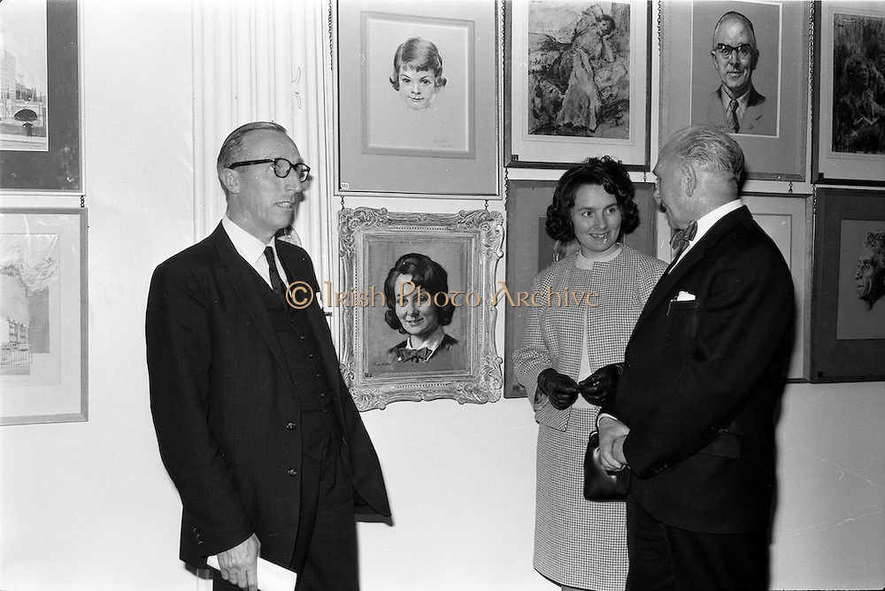06/05/1963<br /> 05/06/1963<br /> 06 May 1963<br /> Opening of the RHA exhibition at the National College of Art, Dublin. It was the 134th exhibition of the Academy. Image shows Dr. Ivor Holloway, Superintendent of the Regional Maternity Hospital, Limerick and his wife viewing her portrait with the artist Mr. George Collie, RHA at the opening.
