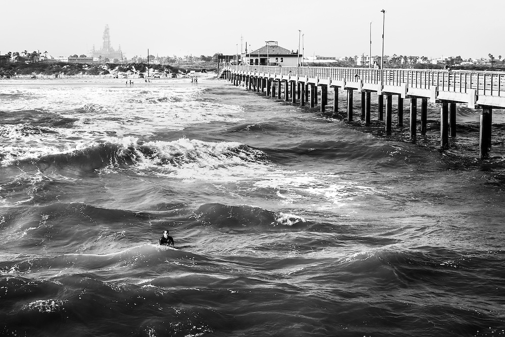 Lonely surfer is waiting for the right wave in Port Aransas, Texas, USA