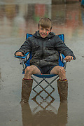 A boy picks an unusual place to place his folding chair. A large puddle left over from teh previous nights rain addsto the problems of moving around  albeit some see it as a leisure facility- 2016 Glastonbury Festival, Worthy Farm, Glastonbury.