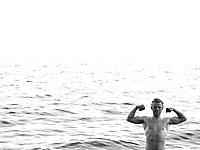 Mann har bada i Baikalsjøen og viser muskler på vei opp av vannet,  Man has been swimming in Baikal, showing muscles