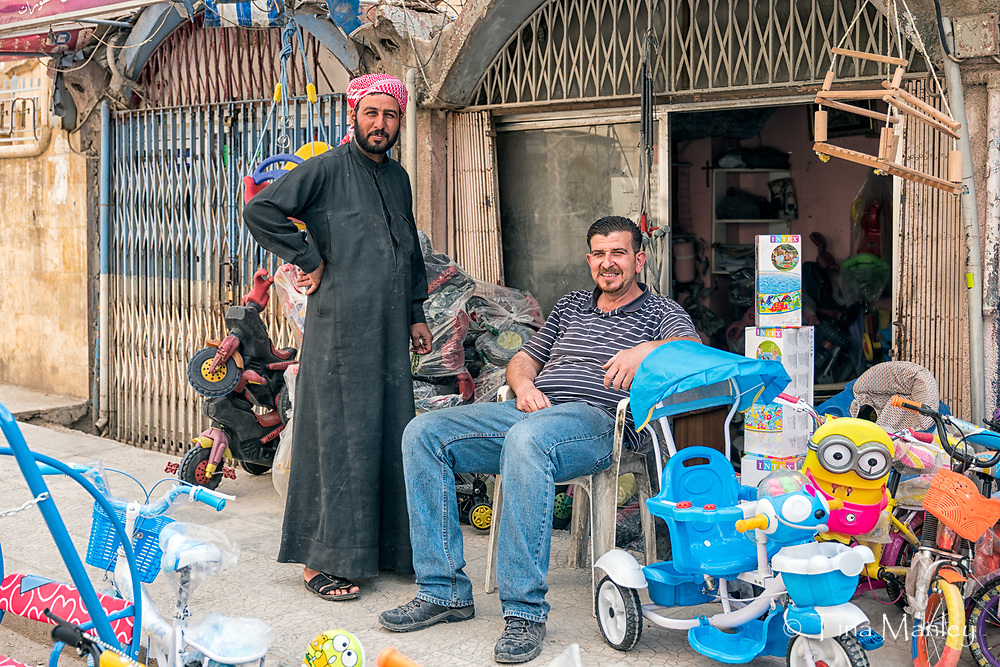 Shop vendors selling children's toys and tricycles in Hasakah, Syria.