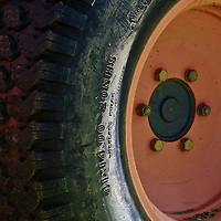 Sidelit image of a worn and muddy tire on a tractor used to maintain the playing fields near the Vienna Community Center, Vienna, Virginia.