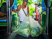 25 NOVEMBER 2017 - YANGON, MYANMAR: A man bringing produce to a local market gets off the Yangon Circular Train. The Yangon Circular Train is a 45.9-kilometre (28.5 mi) 39-station two track loop system connects satellite towns and suburban areas to downtown. The train was built during the British colonial period, the second track was built in 1954. Trains currently run both directions (clockwise and counter-clockwise) around the city. The trains are the least expensive way to get across Yangon and they are very popular with Yangon's working class. About 100,000 people ride the train every day. A a ticket costs 200 Kyat (about .17¢ US) for the entire 28.5 mile loop.    PHOTO BY JACK KURTZ