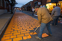Tom Menard and Izzy Brake paint Canal Street orange on Wednesday evening transforming it into PumpCanaly for Pumpkin Fest.  (Karen Bobotas/for the Laconia Daily Sun)