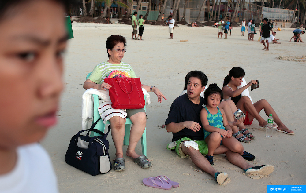 A family of Asian tourists together on the sand at White Beach,  Boracay Island, the Philippines on October 4, 2008, Photo Tim Clayton..Asian tourists at White Beach, Boracay Island, the Philippines...The 4 km stretch of White beach on Boracay Island, the Philippines has been honoured as the best leisure destination in Asia beating popular destinations such as Bali in Indonesia and Sanya in China in a recent survey conducted by an International Travel Magazine with 2.2 million viewers taking part in the online poll...Last year, close to 600,000 visitors visited Boracay with South Korea providing 128,909 visitors followed by Japan, 35,294, USA, 13,362 and China 12,720...A popular destination for South Korean divers and honeymooners, Boracay is now attracting crowds of tourists from mainland China who are arriving in ever increasing numbers. In Asia, China has already overtaken Japan to become the largest source of outland travelers...Boracay's main attraction is 4 km of pristine powder fine white sand and the crystal clear azure water making it a popular destination for Scuba diving with nearly 20 dive centers along White beach. The stretch of shady palm trees separate the beach from the line of hotels, restaurants, bars and cafes. It's pulsating nightlife with the friendly locals make it increasingly popular with the asian tourists...The Boracay sailing boats provide endless tourist entertainment, particularly during the amazing sunsets when the silhouetted sails provide picture postcard scenes along the shoreline...Boracay Island is situated an hours flight from Manila and it's close proximity to South Korea, China, Taiwan and Japan means it is a growing destination for Asian tourists... By 2010, the island of Boracay expects to have 1,000,000 visitors.