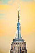 The spire of the Empire State Building photographed against a yellow sky