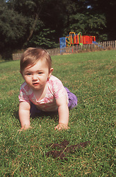 Baby crawling across grass in park near dog foul,