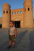 Portrait of a young boy in front of the  the Ota Darvoza gate, Khiva, Uzbekistan, pictured on July 7, 2010, in the late afternoon light of a summer day. Khiva's old city, Ichan Kala, is surrounded by 2.2 kilometres of crenellated and bastioned city walls. Some sections may be 5th century, but the strongest sections were built 1686-88 by Arang Khan. The main gate today is the restored western Ota Darvoza (Father Gate). Khiva, ancient and remote, is the most intact Silk Road city. Ichan Kala, its old town, was the first site in Uzbekistan to become a World Heritage Site(1991). Picture by Manuel Cohen.