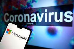 The Microsoft logo seen displayed on a mobile phone with an illustrative model of the Coronavirus displayed on a monitor in the background. Photo credit should read: James Warwick/EMPICS Entertainment