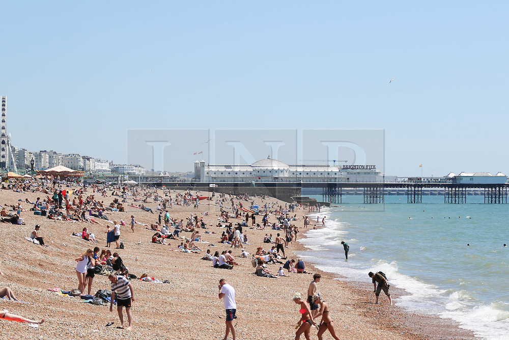 © Licensed to London News Pictures. 03/07/2014. Brighton, UK. People sunbathing on Brighton Beach at lunchtime. Temperatures in parts of the south east are expected to hit 27 degrees this week. Photo credit : Hugo Michiels/LNP
