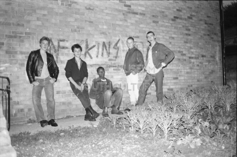 Boys stood in front of SKINS graffiti, UK, 1980s.