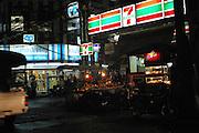 A Seven Eleven shop on a busy street corner of Bangkok, Thailand