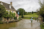 Man wades through flood water in Swinbrook, Oxfordshire, England, United Kingdom