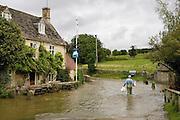 Man wades through flood water in Swinbrook, Oxfordshire, England, United Kingdom