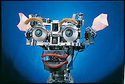 Eyes sweeping the room with what seems to be hopeful curiosity, Kismet the robot sits like an animated bust on Cynthia Breazeal's desk at MIT in Cambridge, MA. When it spots visitors, the robot's expression changes to an almost uncannily convincing expression of interest and delight. From the book Robo sapiens: Evolution of a New Species. One of a series of Kismet images.