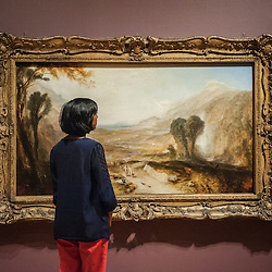 London, UK - 8 September 2014: a gallery assistant looks up at &lsquo;Story of Apollo and Daphne' <br />  by J.M.W. Turner, during the press preview of The EY Exhibition: Late Turner &ndash; Painting Set Free exhibition at Tate Britain