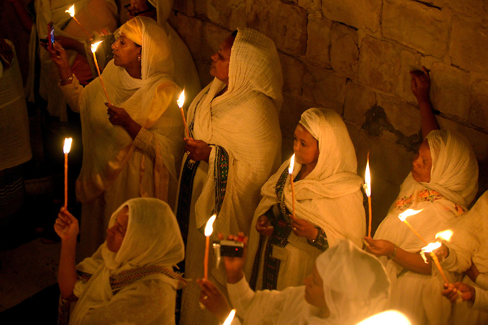 JERUSALEM, ISRAEL - APRIL 19: Ethiopian Christian worshipers Celebrate the Holy Fire ceremony at the Deir Al-Sultan, the Ethiopian section of the Church of the Holy Sepulchre on April 19, 2014 in Jerusalem's old city, Israel. Thousands of Christian pilgrims from around the world have flocked to the City of Jerusalem to mark Holy Fire Ceremony. The ancient fire ritual celebrates the Messiah's resurrection after being crucified on the cross . Photo by Gili Yaari.