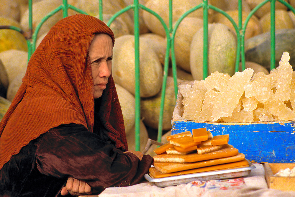 A serious woman in a red shawl sells melons, rock candy, and various other food items, in Kashgar Market, Xinjiang, China.