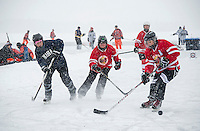 The Lady Jeffs team (Amherst College Alumni) go head to head with the Red Hot Chili Puckers in the women's division during day one of the New England Pond Hockey Classic on Lake Waukewan Friday morning.  (Karen Bobotas/for the Laconia Daily Sun)