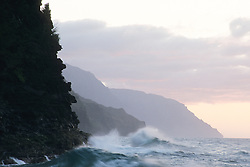 United States, Hawaii, Kauai, ocean waves pounding cliffs at dusk