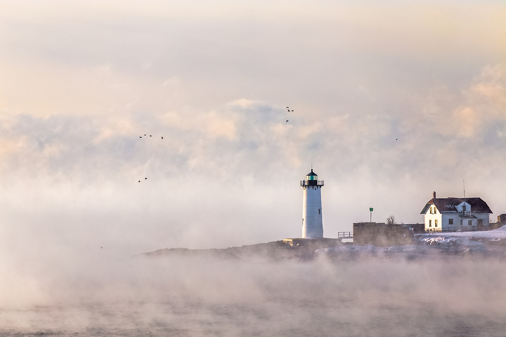 Groups of ducks fly by on a bitter cold morning over the ocean between Kittery and Portsmouth. Portsmouth Harbor Lighthouse can be seen above the sea smoke along with some faint clouds and atmosphere in the background.