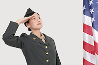 Serious female US military officer saluting American flag over gray background