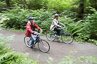 Two people biking in forest elevated view motion blur