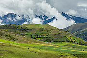 Agricultural fields around the village of Moray and the Andes Mountains rising above Sacred Valley, Peru.