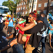 A young female dancer is grabbed by passing lads. The Notting Hill Carnival has been running since 1966 and is every year attended by up to a million people. The carnival is a mix of amazing dance parades and street parties with a distinct Caribbean feel.