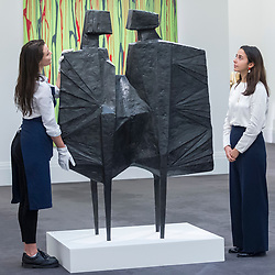 """© Licensed to London News Pictures. 16/11/2018. LONDON, UK. Staff members view """"Two Watchers V Third Version"""" by Lynne Chadwick (Est. GBP400,000-600,000).  Preview of Sotheby's autumn sale of Modern & Post War British art.  Works from the British art scene of the past century will be offered for sale on 20 and 21 November 2018 at Sotheby's in London.  Photo credit: Stephen Chung/LNP"""