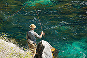 Fly fisherman casting into clearn blue water below the falls in the natural spring water at Box Canyon State Park, Wendell, Idaho.