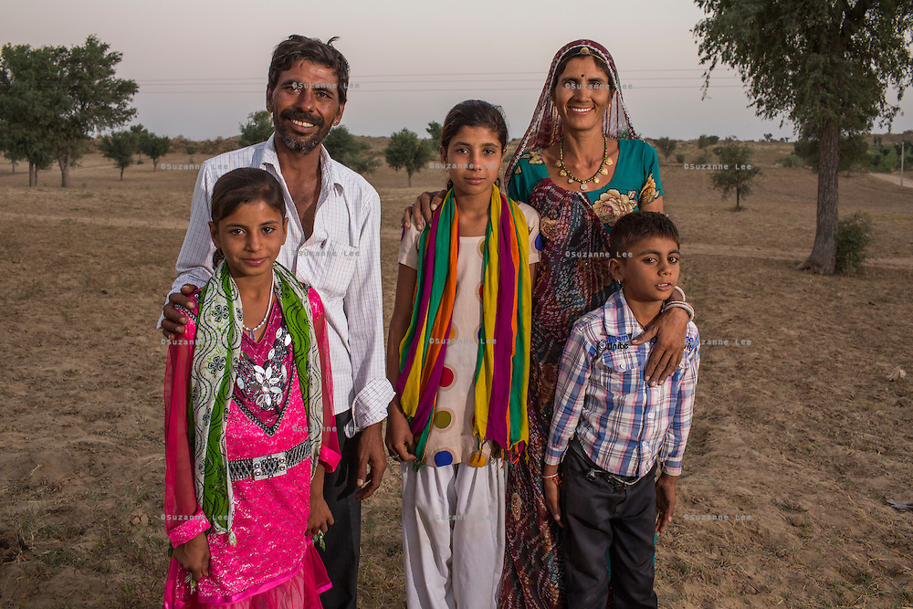 Guar farmers Birbal Ram, 38, and his wife Kelavati Devi, 38, pose for a family portrait with their children Sunil, 8, Priyanka, 10,  and Radha, 12 at their farmhouse in Rajera village, Bikaner, Rajasthan, India on October 23, 2016. Their crop yield has increased by at least fifty percent since intervention work by Technoserve had started. Non-profit organisation Technoserve works with farmers in Bikaner, providing technical support and training, causing increased yield from implementation of good agricultural practices as well as a switch to using better grains better suited to the given climate. Photograph by Suzanne Lee for Technoserve