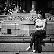 Young woman with her cell phone at Bethesda Fountain in Central Park
