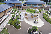 Visitors look around the main display area in the courtyard of  the Saitama Omiya Bonsai Museum of Art in Saitama, Japan on 15 Aug. 2011..Photographer: Robert Gilhooly