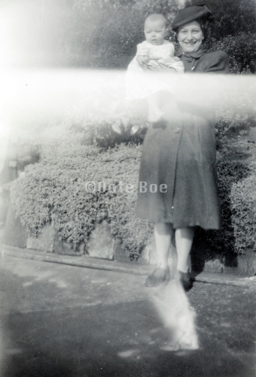 print from negative with a light flair of a happy mother holding her baby