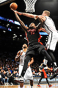 Brooklyn Nets' Mason Plumlee (1) blocks the shot of Toronto Raptors' Amir Johnson (15) during an NBA basketball game on Monday, March 10, 2014 at Barclays Center in New York. (AP Photo/Kathy Kmonicek)