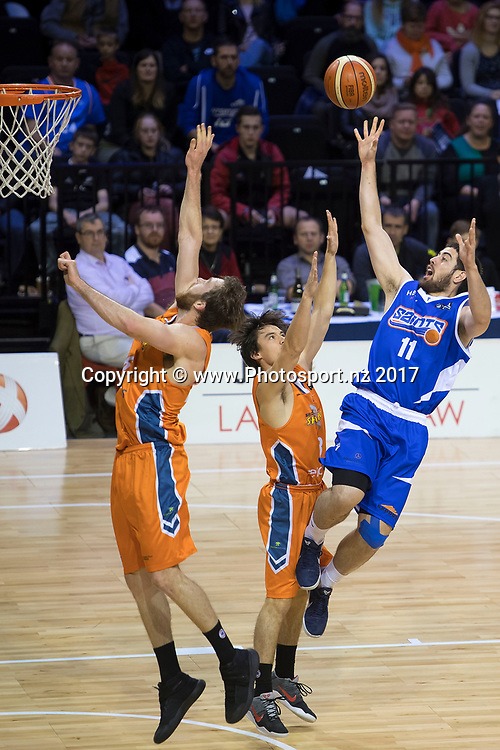 Saints' Jordan Ngatai (R jumps to shoot with Sharks' Nick Kay (L) and Derone Raukawa during the NBL Wellington Saints vs Southland Sharks basketball match at the TSB Arena in Wellington on Friday the 19th of March 2017. Photo by Marty Melville / www.Photosport.nz