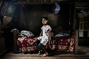 Portrait of Imanhian, 9 on her bed in a  Traditional Kashi House, this house has been here from before 1941, it is not a pine tree, It is made with good wood and all hand made. <br /> Total six people live here. <br /> 